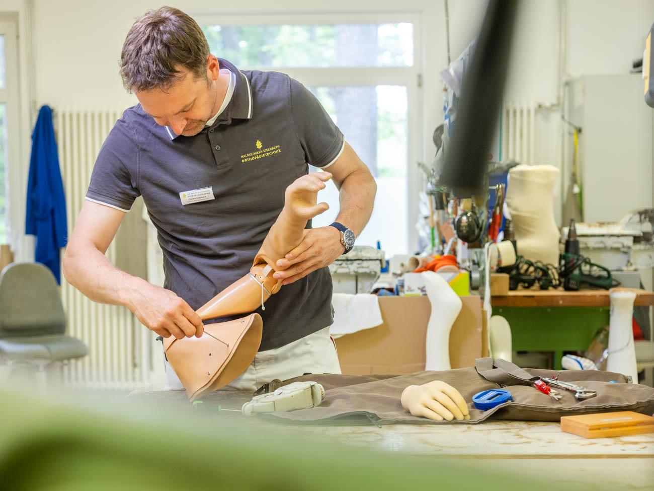 Mitarbeiter passt Handprothese an DSF2024
