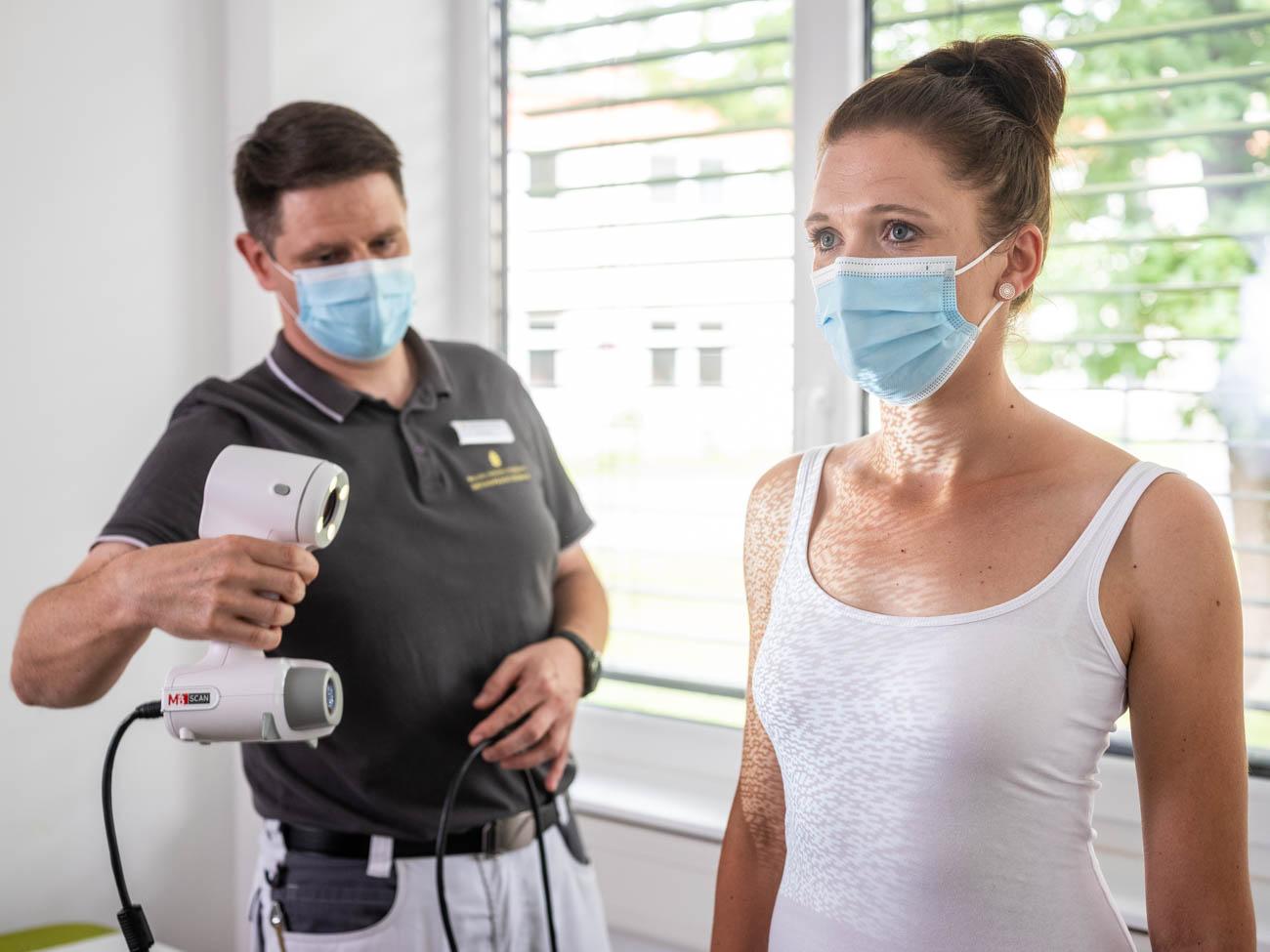 Mitarbeiter scannt Patientin mit Mundschutz DSF1089